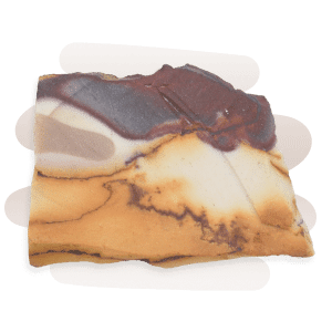 An opaque and rough Mookaite Jasper stone in a blend of cream, brown, yellow and mauve hues.