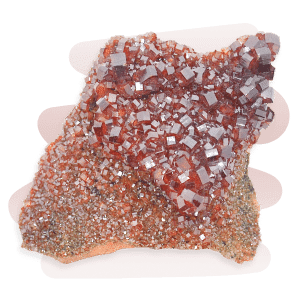 A burnt-orange Vanadinite stone forming in clusters of small hexagonal-shaped prismatic crystals.